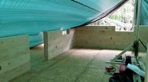 tarp covering logs from weather, log home construction site, pre-cut logs, laminated, kiln dried, Timberhaven, custom built log home, home builder