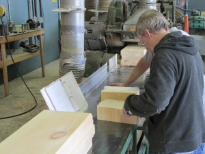 making adjustments to cutting heads on profile machine, laminated logs being loaded onto conveyor, Timberhaven, custom built log home, log homes, log cabin, kiln-dried