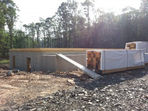 foundation in place subfloor being installed, materials staged on property, post and beam construction, under construction, log homes, log cabins, log cabin kits, Timberhaven, post and beam cabin, post and beam cabin kits, kiln dried, laminated