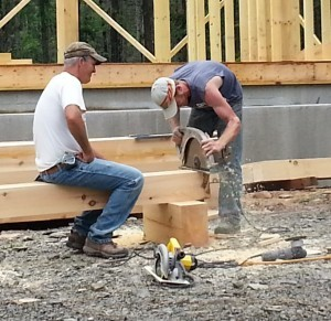 crew uses large circular saw to cut posts for post and beam project under construction, log homes, log cabins, log cabin kits, Timberhaven, post and beam cabin, post and beam cabin kits, kiln dried, laminated