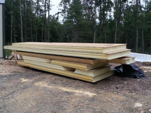 SIPs untarped and staged in preparation for installation, custom post and beam home, post and beam homes, under construction, log homes, log cabin, log cabin kits, Timberhaven Log Homes, laminated, kiln dried, heavy timbers, SIPs