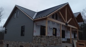 front part of home with new metal roof, post and beam custom home, under construction, Timberhaven, log homes, log cabins, log cabin kits, contemporary siding, black standing seam metal, stone accents on home, laminated, kiln dried, custom post and beam home
