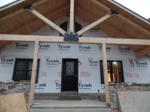 front porch to custom home, post and beam custom home, under construction, Timberhaven, log homes, log cabins, log cabin kits, contemporary siding, black standing seam metal, stone accents on home, laminated, kiln dried, custom post and beam home