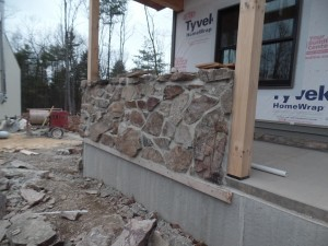 side of porch with solid wall with real mountain stone, post and beam custom home, under construction, Timberhaven, log homes, log cabins, log cabin kits, contemporary siding, black standing seam metal, stone accents on home, laminated, kiln dried, custom post and beam home