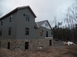 rear of home with mountain stone and siding application, post and beam custom home, under construction, Timberhaven, log homes, log cabins, log cabin kits, contemporary siding, black standing seam metal, stone accents on home, laminated, kiln dried, custom post and beam home