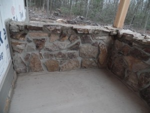 solid wall with real mountain stone, post and beam custom home, under construction, Timberhaven, log homes, log cabins, log cabin kits, contemporary siding, black standing seam metal, stone accents on home, laminated, kiln dried, custom post and beam home