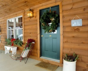 front porch of log home decorated for Christmas, Timberhaven log homes, log homes, log cabin kits, log cabins, Merry Christmas, stone fireplace, fireplace in dining room, natural light, white pine