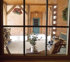 looking through the window at front porch of log home, timberhaven log homes, log homes, log cabin kits, log cabins, Merry Christmas, stone fireplace, fireplace in dining room, natural light, white pine