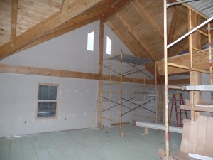 wide open space in kitchen and dining areas, dry wall installation, beam and purlin roof system, post and beam, custom home, log homes, log cabins, log cabin kits, Timberhaven, laminated, kiln dried, under construction, PA log home producer