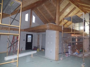 wide open space in main living area and loft, beam and purlin roof system, post and beam, custom home, log homes, log cabins, log cabin kits, Timberhaven, laminated, kiln dried, under construction, PA log home producer, dry wall installation