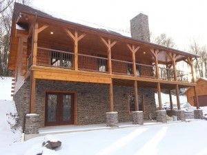 exterior of custom log home with walk-out basement and stone pillars, Timberhaven Log Homes, Valley View, floor plan ideas, complete customization, laminated logs, engineered logs, kiln dried logs, design services, Pennsylvania, log homes, log cabins, log cabin kits, log cabin homes, log home packages