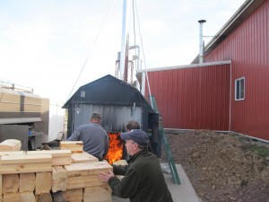 waste material being loaded into an outdoor wood burner, Timberhaven Log Homes, log homes, log cabin homes, log cabins, post and beam homes, timberframe homes, timber frame homes, laminated logs, engineered logs, floor plan designs, kiln dried logs, nature friendly