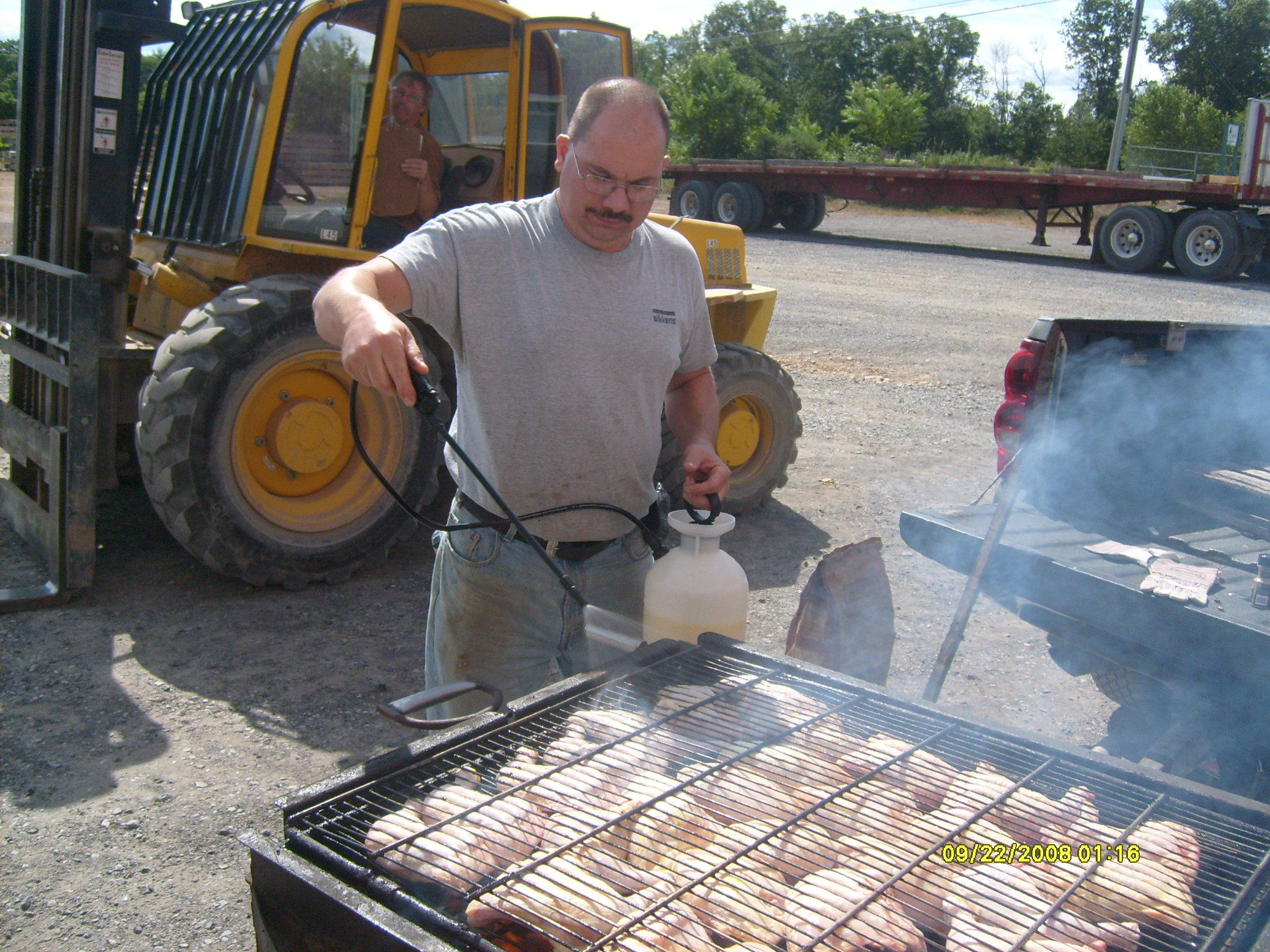 Randy grilling BBQ chicken on nice summer day, employee spotlight, Randy Beachel, Timberhaven Log Homes, log homes, log cabin homes, log cabins, post and beam homes, timberframe homes, timber frame homes, laminated logs, engineered logs, floor plan designs, kiln dried logs