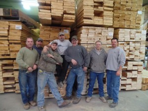 guys in cut shop grouped together by stacks of lumber, employee spotlight, Randy Beachel, Timberhaven Log Homes, log homes, log cabin homes, log cabins, post and beam homes, timberframe homes, timber frame homes, laminated logs, engineered logs, floor plan designs, kiln dried logs