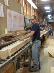 Randy double checking the length of a laminated log cut, employee spotlight, Randy Beachel, Timberhaven Log Homes, log homes, log cabin homes, log cabins, post and beam homes, timberframe homes, timber frame homes, laminated logs, engineered logs, floor plan designs, kiln dried logs