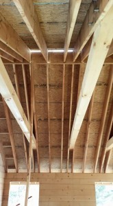 underside of roof showing rafters and ridge beam, roof being constructed on a log home, beautiful bedroom in log home, Timberhaven Log Homes, log homes, log cabin homes, log cabins, post and beam homes, timberframe homes, timber frame homes, laminated logs, engineered logs, floor plan designs, kiln dried logs, Flury Builders, Joe Walsh, Timberhaven local reps, log homes in Massachusetts, log homes in Rhode Island, MA, RI, log home builders, 2x12 rafter roof system