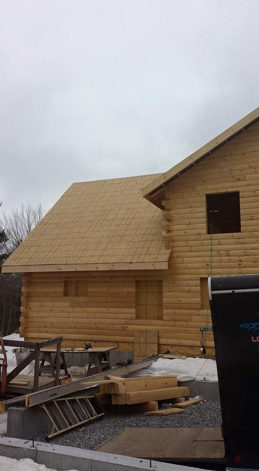 Log home 2x12 rafter roof system under construction for Log cabin roof construction