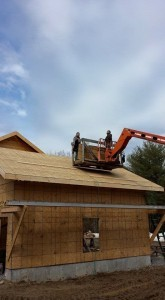 builders using lift to finish OSB sheathing application to garage roof, two-car garage, Timberhaven Log Homes, log homes, log cabin homes, log cabins, post and beam homes, timberframe homes, timber frame homes, laminated logs, engineered logs, floor plan designs, kiln dried logs, Flury Builders, Joe Walsh, Timberhaven local reps, log homes in Massachusetts, log homes in Rhode Island, MA, RI, log home builders