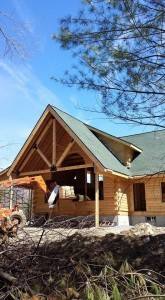 gable end of log home under construction with new shingles, Tamko, log home roof, Timberhaven Log Homes, log homes, log cabin homes, log cabins, post and beam homes, timberframe homes, timber frame homes, laminated logs, engineered logs, floor plan designs, kiln dried logs, Flury Builders, Joe Walsh, Timberhaven local reps, log homes in Massachusetts, log homes in Rhode Island, MA, RI, log home builders