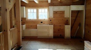 white kitchen cabinets installed in log home, Log home kitchen, Timberhaven Log Homes, log homes, log cabin homes, log cabins, post and beam homes, timberframe homes, timber frame homes, laminated logs, engineered logs, floor plan designs, kiln dried logs, Timberhaven local reps, log homes in PA, log home builders