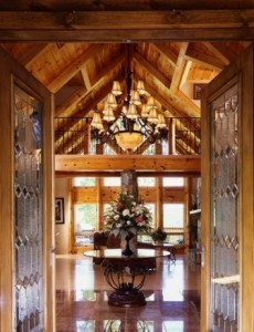 door opening to luxurious log homes, wrought iron table and ballisters, grand chandelier in log home, ultimate home, ultimate log home, Log home kitchens, Timberhaven Log Homes, log homes, log cabin homes, log cabins, post and beam homes, timberframe homes, timber frame homes, laminated logs, engineered logs, floor plan designs, kiln dried logs, Timberhaven local reps, log homes in PA, log home builders