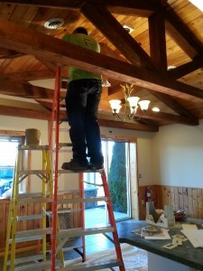 guy working on lights in entryway of new building, Big move, Timberhaven Log Homes, Timberhaven Log & Timber Homes, log homes, log cabin homes, log cabins, post and beam homes, timberframe homes, timber frame homes, laminated logs, engineered logs, floor plan designs, kiln dried logs, Timberhaven local reps, log homes in PA