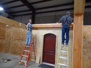two guys on ladders building a display, making great progress, log homes, log cabin homes, log cabins, post and beam homes, timberframe homes, timber frame homes, laminated logs, engineered logs, floor plan designs, kiln dried logs, Timberhaven local reps, log homes in Pennsylvania, log homes in PA, Timberhaven Log Homes, Timberhaven Log & Timber Homes