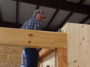 guy placing beam for engineered log display, making great progress, log homes, log cabin homes, log cabins, post and beam homes, timberframe homes, timber frame homes, laminated logs, engineered logs, floor plan designs, kiln dried logs, Timberhaven local reps, log homes in Pennsylvania, log homes in PA, Timberhaven Log Homes, Timberhaven Log & Timber Homes