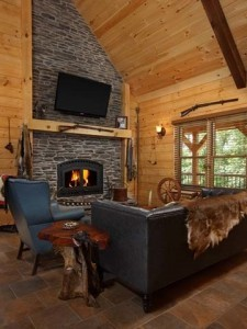 living room with stone fireplace, flat screen TV on fireplace mantel, cabin living, log homes, log cabin homes, log cabins, post and beam homes, timberframe homes, timber frame homes, laminated logs, engineered logs, floor plan designs, kiln dried logs, Timberhaven local reps, log homes in Pennsylvania, log homes in PA, Timberhaven Log Homes, Timberhaven Log & Timber Homes