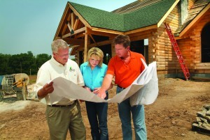 couple working with builder at construction site holding set of plans, find right builder, log homes, log cabin homes, log cabins, post and beam homes, timberframe homes, timber frame homes, laminated logs, engineered logs, floor plan designs, kiln dried logs, Timberhaven local reps, log homes in Pennsylvania, log homes in PA, Timberhaven Log Homes, Timberhaven Log & Timber Homes