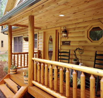 Log Home Porch with Rustic Rail Treatment Illustrates the Use of Natural Building Components in Log Home Construction