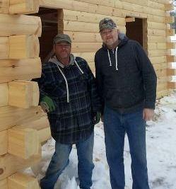 two guys standing by a log home, built in the winter, winter build, building a log home in the winter, Timberhaven, log homes, timber frame homes, under construction