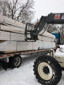 unloading truck of materials, built in the winter, road covered with snow, log home winter, winter build, building a log home in the winter, building a timber frame home in the winter, Timberhaven