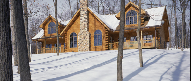 Traditional style log home in the snow.