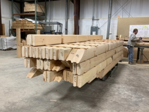 stacked logs in manufacturing facility, New Model Log Home Delivery, log home delivery, delivery day, log homes, Timberhaven, local reps, model home in TN