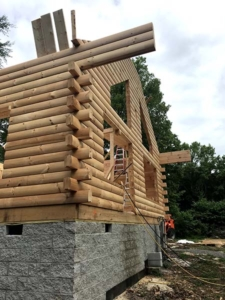 mortise and tenon corners on logs, log walls, new model log home under construction