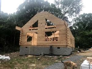 log home being built, solid gables, log walls, new model log home under construction
